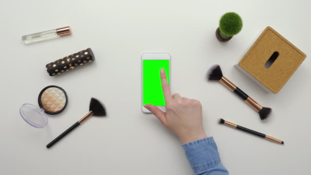 Top-View-Overhead-Of-Woman-Using-Smartphone-By-Beauty-Products