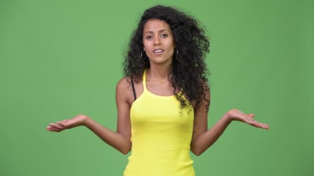 Young-beautiful-Hispanic-woman-shrugging-shoulders