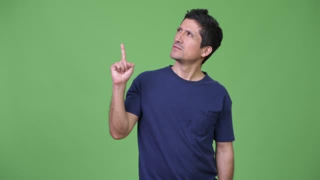 Hispanic-man-thinking-while-pointing-finger-up