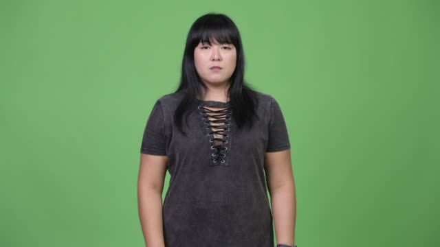 Beautiful-overweight-Asian-woman-covering-mouth-as-three-wise-monkeys-concept