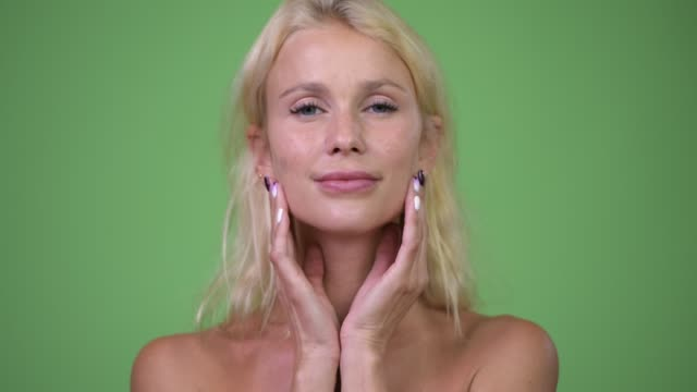 Head-shot-of-young-beautiful-blonde-woman-shirtless-while-touching-her-face