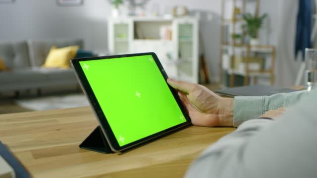 Sobre-el-hombro-de-una-explotación-del-hombre-y-observando-maqueta-verde-pantalla-Digital-Tablet-PC-mientras-está-sentado-en-el-escritorio-En-el-fondo-acogedora-sala-de-estar-