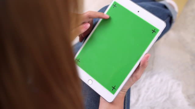 Young-asian-woman-using-black-tablet-device-with-green-screen-Asian-woman-holding-tablet-scrolling-pages-while-sitting-on-the-couch-in-the-living-room-Chroma-key-