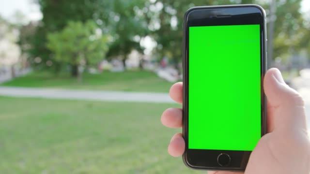 Una-mano-sosteniendo-un-teléfono-con-una-pantalla-verde