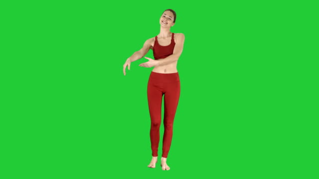 Young-woman-stretching-hands-in-yoga-dress-on-a-Green-Screen-Chroma-Key