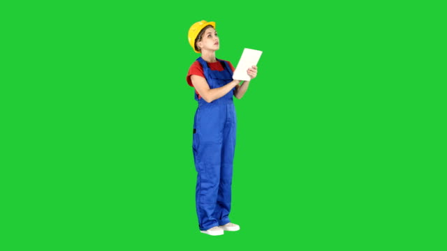 Female-engineer-in-yellow-safety-helmet-is-looking-to-tablet-computer-while-checking-for-construction-building-on-a-Green-Screen-Chroma-Key