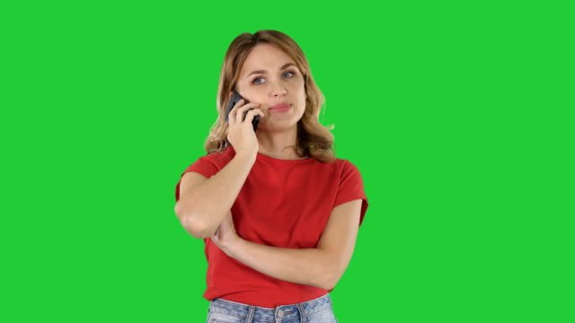 Young-beautiful-woman-in-red-t-shirt-speaks-on-mobile-phone-on-a-Green-Screen-Chroma-Key
