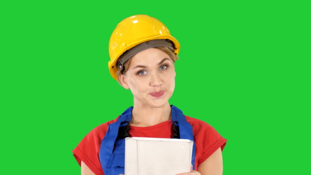 Young-construction-worker-with-tablet-computer-presenting-something-on-a-Green-Screen-Chroma-Key