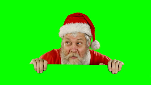 Surprised-santa-claus-hiding-behind-green-screen