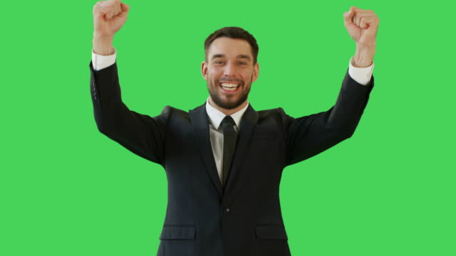 Medium-Shot-of-a-Handsome-Businessman-Making-Win-Gestures-and-Rejoycing-Celebrating-His-Success-Background-is-Green-Screen-