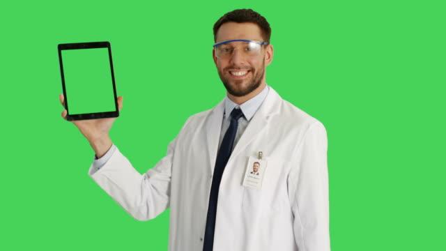 Tiro-medio-de-un-científico-guapo-vistiendo-gafas-protectoras-sosteniendo-una-tableta-con-una-mano-y-haciendo-deslizar-gestos-tocando-con-otro-La-tableta-y-el-fondo-son-pantalla-verde-