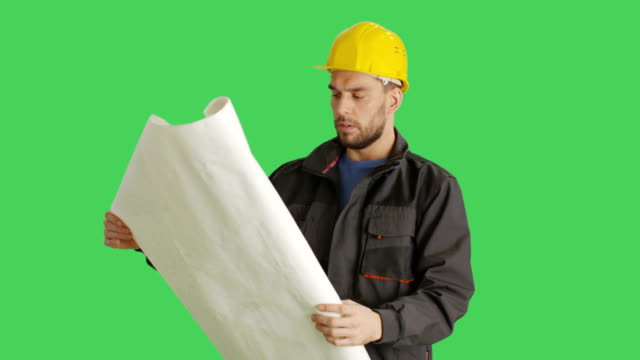 Mid-Shot-of-a-Worker-Wearing-Hard-Hat-Looks-and-Plans-and-Blueprints-Background-is-Green-Screen-