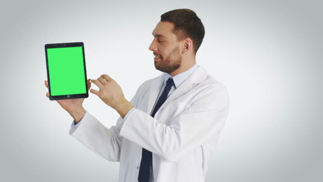 Mid-Shot-of-a-Handsome-Doctor-Holding-Tablet-Computer-with-One-Hand-and-Making-Swiping-Touching-Gestures-with-Another-Tablet-Has-Green-Screen-Shot-with-White-Background-