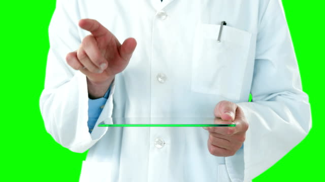 Doctor-using-futuristic-tablet-against-green-screen