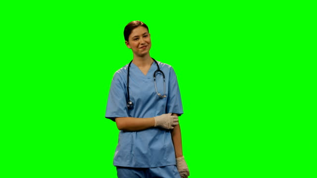 Happy-female-surgeon-standing-against-green-screen