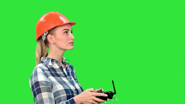 Female-engineer-operating-a-drone-analyzing-object-on-a-Green-Screen-Chroma-Key