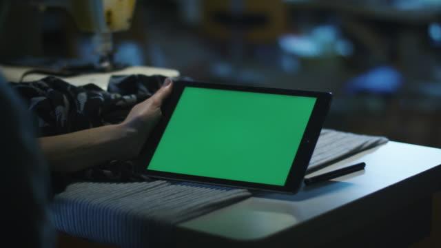 Seamstress-hält-ein-Tablet-mit-einem-Mock-up-Bildschirm-im-Landschaftsmodus-