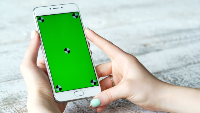 Young-woman-uses-smartphone-with-green-screen