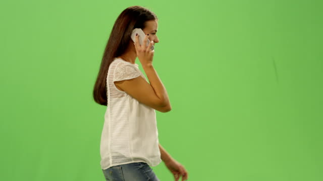 Casual-young-brunette-girl-is-walking-and-talking-on-the-phone-on-a-mock-up-green-screen-in-the-background-