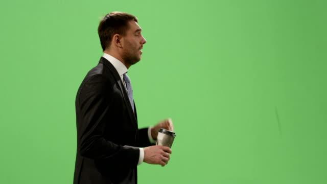Müde-Geschäftsmann-im-Anzug-ist-zu-Fuß-mit-einem-Kaffee-auf-ein-Mock-up-green-Screen-im-Hintergrund-