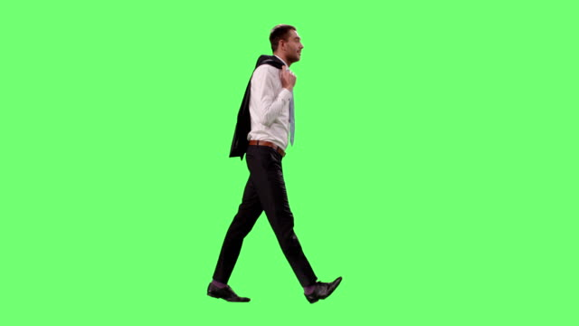 Young-Successful-Businessman-in-a-Suit-Enjoys-Good-Weather-Throws-Jacket-over-the-Shoulder-While-Walking-Shot-on-Mock-up-Green-Screen-