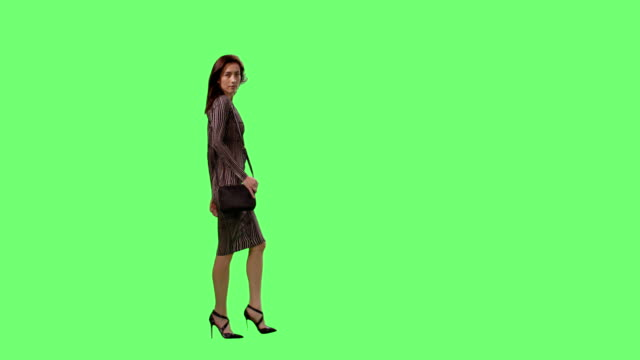 Glamorous-Brunette-Female-in-a-Tight-Dress-with-a-Small-Purse-Gracefully-Walking-on-a-Mock-up-Green-Screen-in-the-Background-
