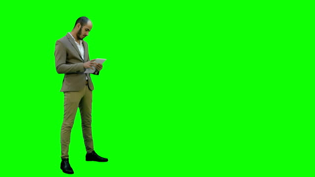 Young-businessman-using-digital-tablet-on-a-Green-Screen-Chroma-Key