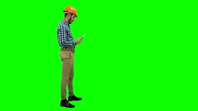 Ingeniero-contratista-inspeccionar-obra-con-tableta-digital-en-una-pantalla-verde-Chroma-Key