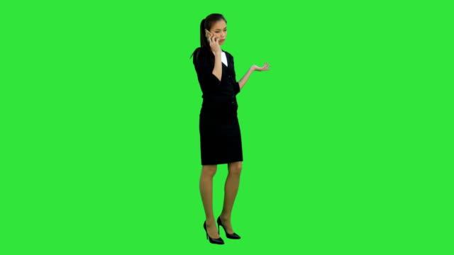 Escéptica-e-infeliz-mujer-joven-hablando-por-teléfono-móvil-en-una-pantalla-verde-Chroma-Key