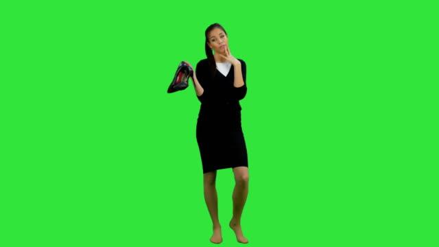 Müde-junge-Geschäftsfrau-steht-barfuß-und-Holding-high-Heels-Schuhe-auf-einem-Green-Screen-Chroma-Key