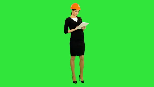 Female-architect-in-hardhat-holding-tablet-and-making-inspection-on-a-Green-Screen-Chroma-Key