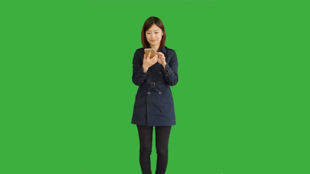Young-Asian-Woman-Wearing-a-Blue-Coat-Using-Smartphone-Digital-Tablet-and-Looking-at-Camera-Woman-Standing-in-Front-of-a-Green-Screen-for-Chroma-Key-