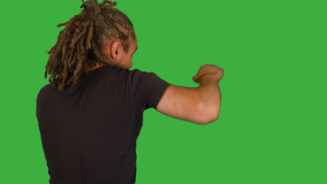 Mid-Aged-Man-Fighting-in-Front-of-a-Green-Screen-Preparing-for-Combat-and-Beating-towards-Camera-Dreadlocks-and-Black-T-Shirt-