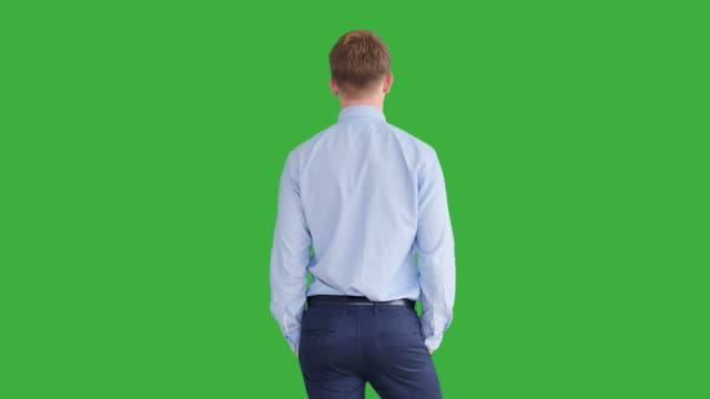 Young-Handsome-Men-Acting-in-Front-of-a-Green-Screen-Blond-Hair-Blue-Shirt-and-Blue-Trousers-Dancing-Thinking-Turning-Around-and-Talking-to-the-Camera-