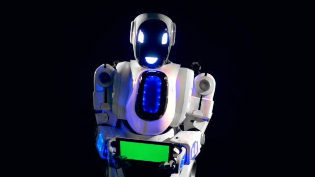 White-robot-turns-to-camera-holding-a-green-screen-board-