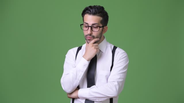 Young-handsome-bearded-Persian-businessman-against-green-background