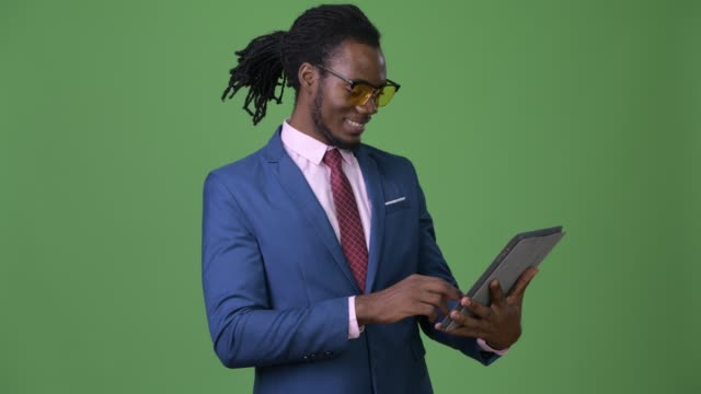 Young-handsome-African-businessman-with-dreadlocks-against-green-background