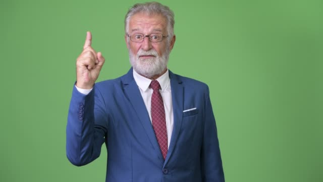 Handsome-senior-bearded-businessman-against-green-background