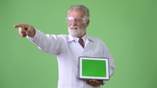 Handsome-senior-bearded-man-doctor-against-green-background