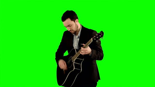 Joven-tocando-la-guitarra-en-una-pantalla-verde