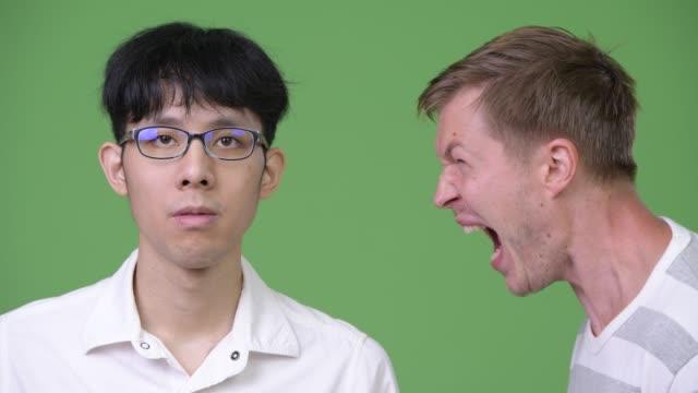 Joven-empresario-escandinavo-enojado-gritando-en-el-joven-empresario-asiático