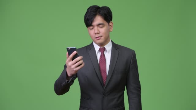 Young-handsome-Asian-businessman-using-mobile-phone