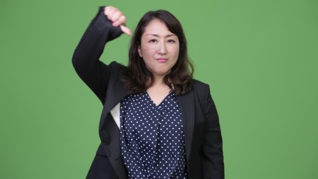 Mature-beautiful-Asian-businesswoman-giving-thumbs-down