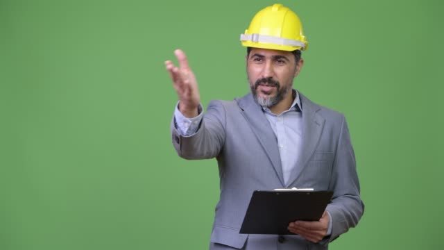 Handsome-Persian-bearded-businessman-as-engineer-directing-with-clipboard
