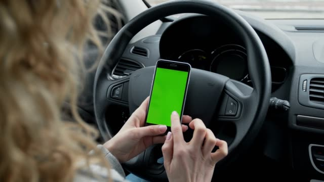 Woman-sits-in-the-modern-car-and-works-on-smartphone---closeup-hands-Green-screen-Chroma-key