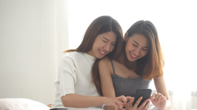 Beautiful-young-asian-women-LGBT-lesbian-happy-couple-sitting-on-bed-hug-and-using-phone-together-bedroom-at-home-LGBT-lesbian-couple-together-indoors-concept-Spending-nice-time-at-home-