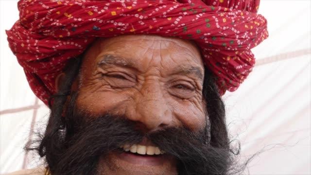 Cerrar-sonriente-hombre-de-Rajasthan-saluda-con-gran-bigote-que-llevaba-un-vestido-rojo-de-turbante-y-tradición