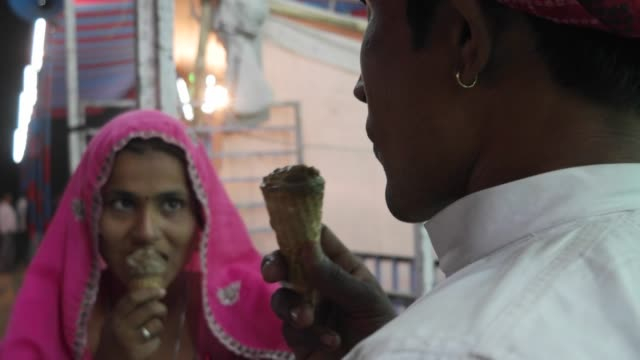 Indian-couple-eating-ice-cream-in-traditional-dresses-at-the-Pushkar-Mela-a-carnival-of-Rajasthan-India