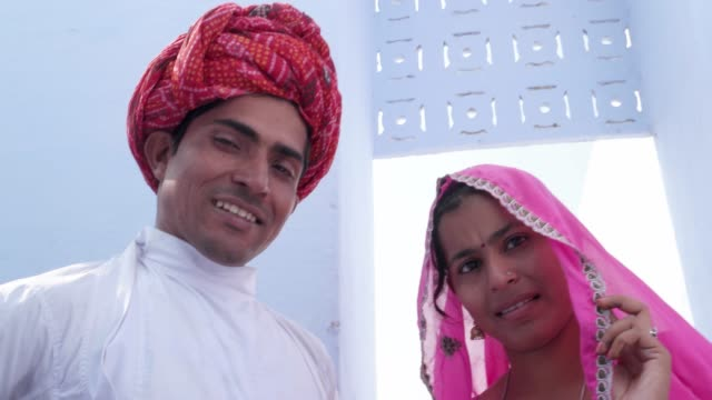 Handheld-Tilt-up-to-portrait-of-newly-wed-bride-in-pink-sari-and-groom-in-red-turban-walking-away-in-Rajasthan-India