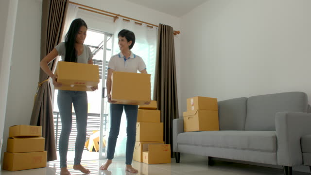 Happy-asian-women-LGBT-lesbian-couple-holding-boxes-entering-new-modern-house